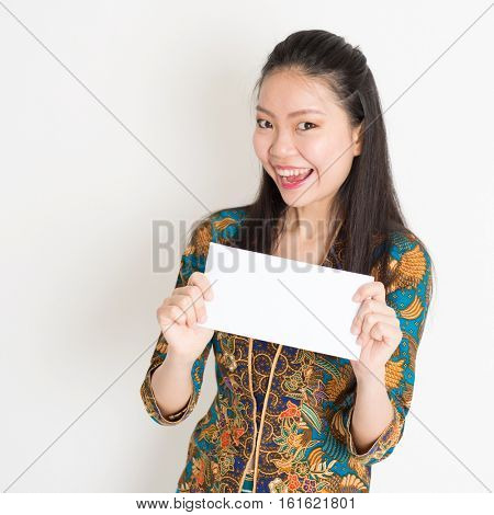 Portrait of young southeast Asian girl in traditional Malay batik kebaya dress hand holding a white blank paper card with surprised face expression, standing on plain background.