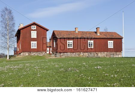 ALFTA, SWEDEN ON MAY 11. View of buildings belonging to Loka farm, Homestead on May 11, 2013 in Alfta, Sweden. Old wooden, log building on a hill. Sunny evening. Editorial use.