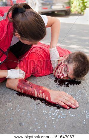 Paramedic checking pulse on hit-and-run victim, color image
