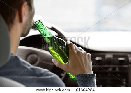 Man drinking beer while driving car, closeup. Don't drink and drive concept