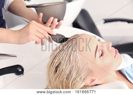 Hairdresser putting mask on woman's hair in salon
