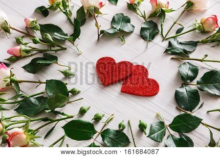 Valentine background with pink rose flowers and wooden glitter hearts, top view on white rustic wood. Happy lovers day mockup, copy space