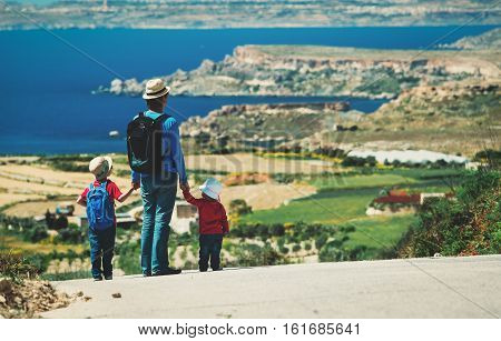 father with two kids walking on scenic road, family travel