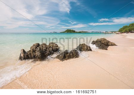 Clear water beach of blue sea with black rock and moving wave on sunny day in Thailand. Cloudy blue sky as background.
