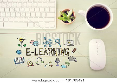 E-Learning concept with workstation on a light green wooden desk