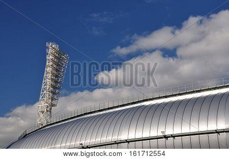 Spotlight at the stadium against the blue sky.