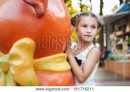 little girl hides behind an orange statue