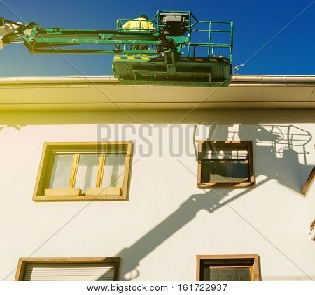 Worker on the modern hydraulic mobile construction platform elevated on the last floor of a house with construction worker preparing to to work
