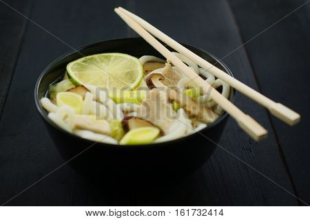 Japanese food: soup with udon noodles chicken mushrooms leeks and lime. Concept of eating. Concept of asian food. Concept of japanese food. Selective focus on center of lime.