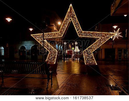 The star and the throne. Lodz, Poland - December 09, 2016 Illuminated Christmas star and a throne for Santa Claus on the street Piotrkowska.