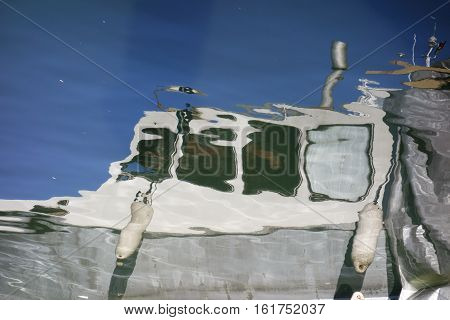 Reflection of a white fishing boat from sea water in Helsinki Finland during Helsinki Baltic Herring Fair in 8 October 2015.