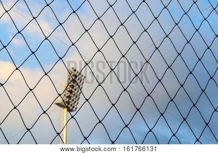 Black soccer net texture against blue sky and spotlight pole background