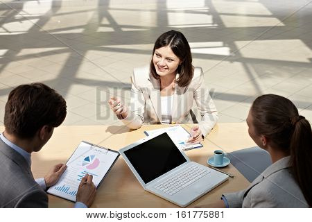 Young businesswoman explaining business task to her subordinates