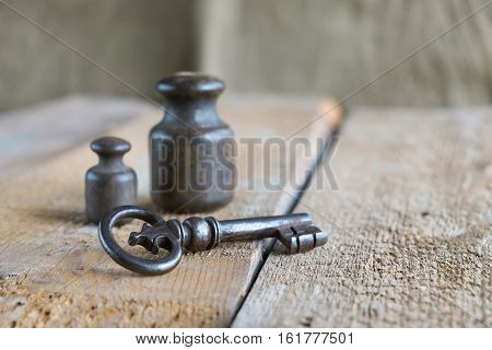 Two old weights and key on an old wooden table. Texture background exterior