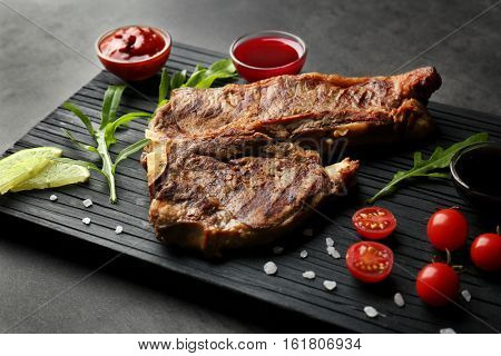 Composition of tasty steak and ingredients on kitchen table
