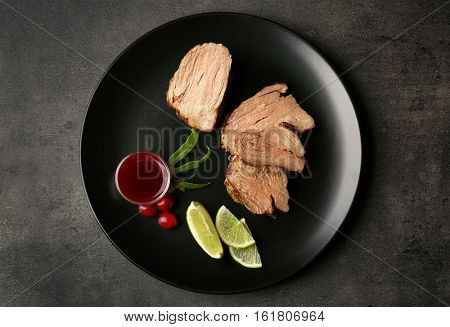 Plate with tasty steak and some ingredients on kitchen table