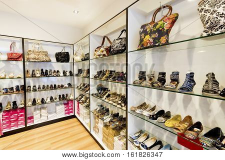 Modern shoe shop with ladies and gents items in leather beside bags sandals shoes boots with packages on the shelves in a luxury showroom