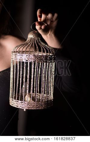 A Golden cage in feminine hand on dark background. A symbol of freedom and bondage in a rich marriage.