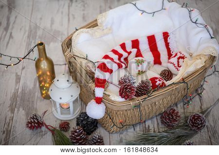 Christmas decorations of colored cones basket lights garland and Christmas balls and knitted cap on a light gray wooden background