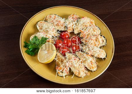 Seafood. Top view of shellfish mussels baked with cheese served with cherry tomatoes and lemon