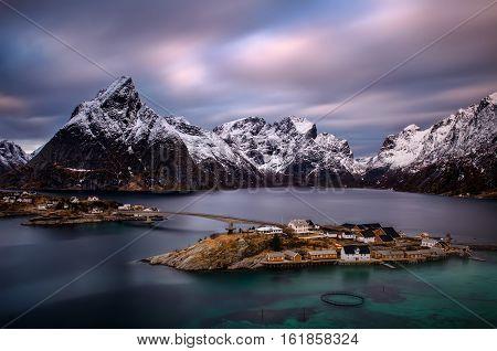 Sakrisoya island with rorbu at Reinefjorden with snowy mountains in background Lofoten