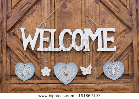Wooden welcome sign on door decorated with hearts flowers and butterfly