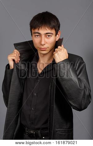 Young stylish brunet man in black shirt and black leather coat stands on grey background with collar raised.