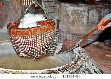 Boiling rock salt Lapping crystallized salt from boiled saltwater to dried up the basket. Nan Thailand. Selective focus.