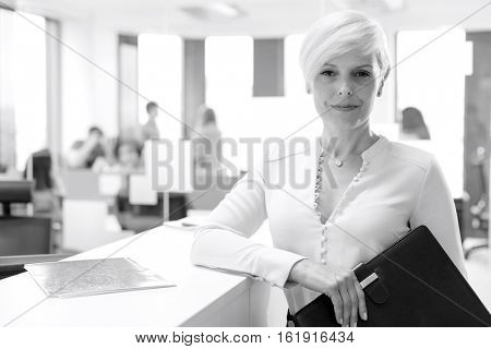 Portrait of confident mature businesswoman holding file in office
