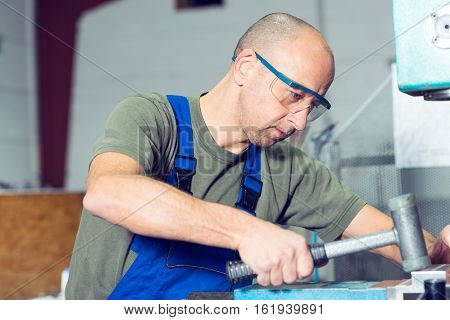 Worker In Factory On Work Bench With Hammer