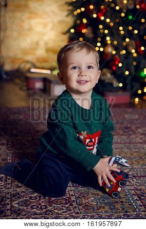 baby boy sitting near Christmas tree and a toy in the hands