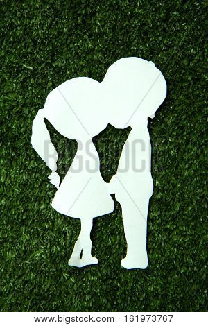 Paper cut of two lovers on green grass, paper cut style.
