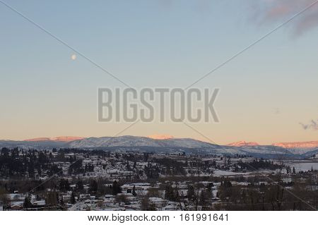 Winter landscape of mountains at sunset with orange sunshine on mountain tops and bright white snow covered peaks. Trees,snow,houses and road in valley. Clear bright clear sky with moon and isolated cloud.