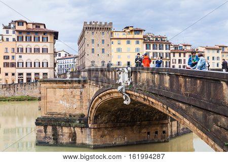 Tourists On Ponte Santa Trinita Over Arno River