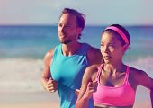 Couple athletes runners running on beach. Interracial young adults asian woman, caucasian man, train poster