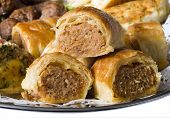 image of junk food  - Close up of mini party sausage rolls on a hot food platter with savoury meatballs and quiche - JPG
