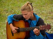 stock photo of musical instrument string  - hiker girl playing guitar camping hiking musical instrument - JPG