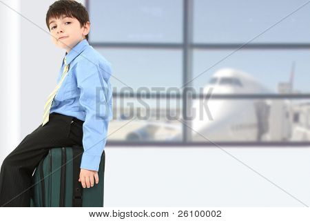 Adorable seven year old french american boy sitting on suitcase at airport.