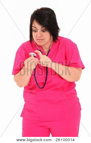 Attractive forty year old over weight nurse in pink scrubs with Stethoscope over white background.  Checking to see if stethoscope works.