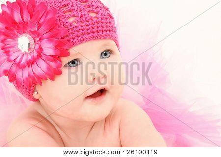 Hermosa chica de american baby de 4 meses de edad en el sombrero de flores y tutu sobre fondo blanco.