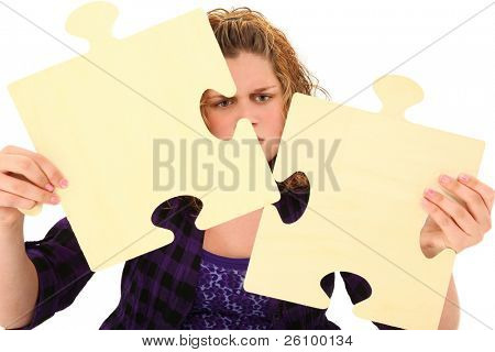 Beautiful american 13 year old teenager with confused face holding giant wooden puzzle pieces over white background.