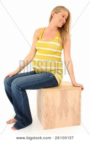 Beautiful 19 year old pregnant american woman sitting on wooden box over white background.