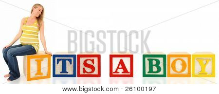 Beautiful 19 year old pregnant american woman sitting on wooden box over white background.  It's A Boy in alphabetical blocks.