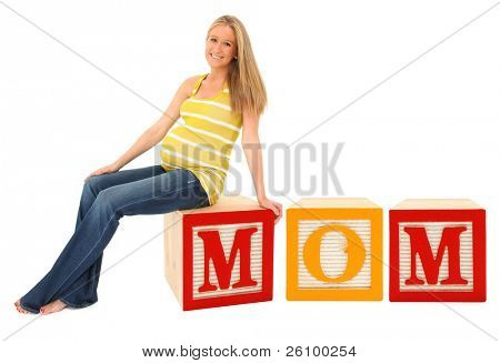 Beautiful 19 year old pregnant woman sitting on alphabet blocks spelling word mom.