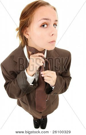 Beautiful 16 year old teen girl in over sized baggy suit fixing tie over white background.