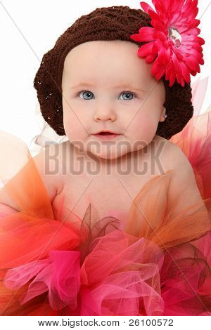 Adorable 5 month old baby girl wearing pink and brown tutu over white.