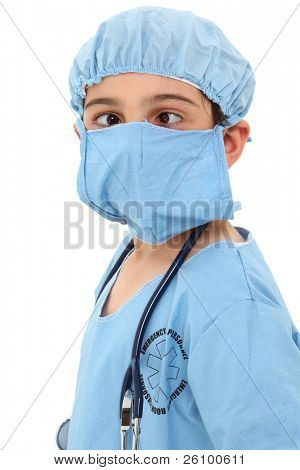 Adorable 7 year old french american boy making crossed eyes in surgeon scrub over white.