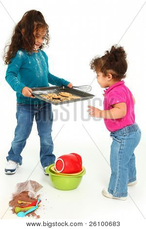 Adorable 3 year old Hispanic-African American girl, baking cookies over white background.  Giving cookies to little sister.