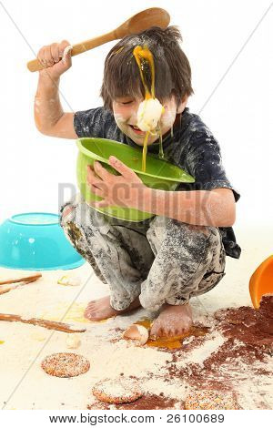 Adorable 7 year old boy making mess baking cookies.
