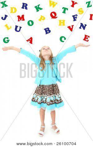 Adorable six year old girl tossing colorful alphabet into the air over white background.